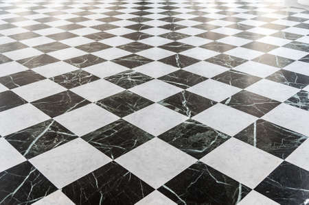 Black and white checkered marble floor with sunlight