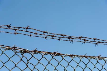 Wired fence with barbed wires on a blue sky