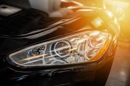 Closeup on an headlight of a black sport car in the sunlight Imagens