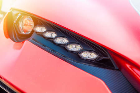 Close up of a red sport luxury car in sunset background