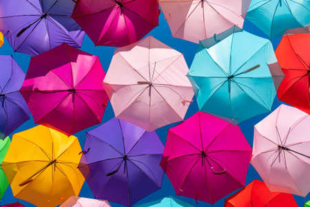 Colorful umbrellas background on a blue sky