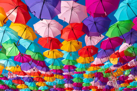 Colorful umbrellas background om a blue sky