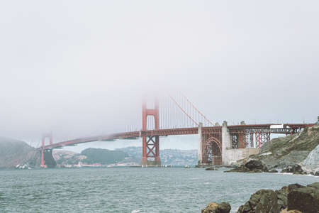 View of Golden Gate Bridge in the fog from the near beach
