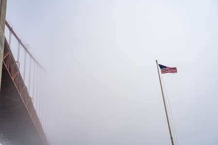 Golden Gate bridge and USA flag in the fog