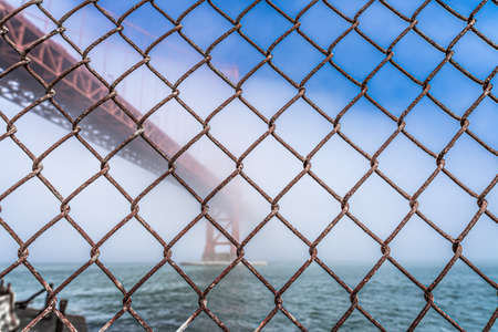 Dramatic Golden Gate Bridge through fence