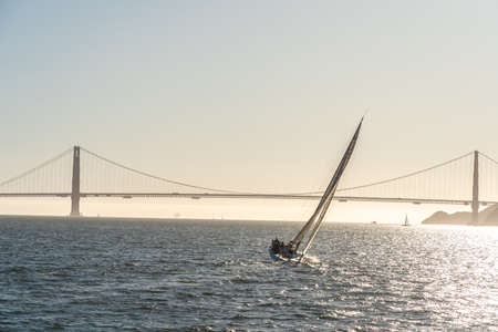 Beautiful yacht in San Francisco bay at sunset, Golden Gate bridge on the horizon.