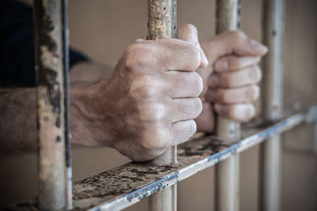 Close up of prisoner hands in jail.