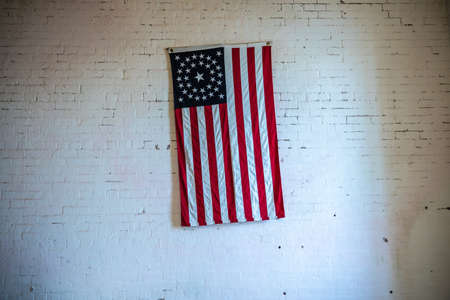 Old USA flag on a white brick wall.