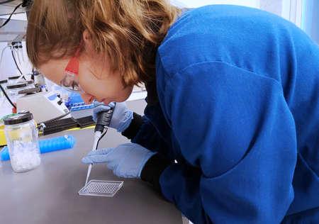 Jeune chercheuse chargeant la pipette avec un échantillon d'ADN pour charger un gel d'agarose. Femme en sciences.