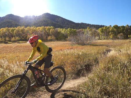 Asian guy with yellow jacket riding a bike around Sardine Peak Trailhead, Ogden, Utah, United States. In motion photo.