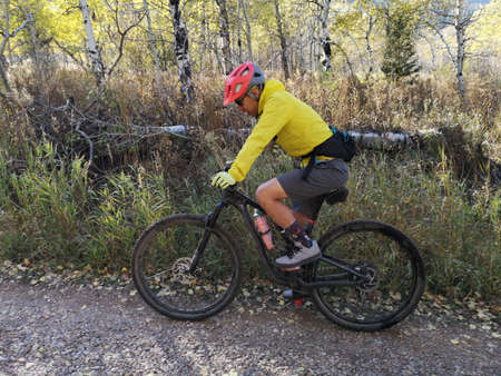 Asian guy with a red helmet and yellow jacket riding a bike around Sardine Peak Trailhead, Ogden, Utah, United States. In motion photo. Reklamní fotografie
