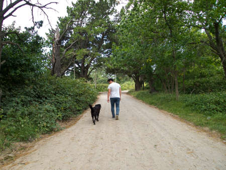 Young man looking to a black labrador dog, while both walking on a path, Tandil, Buenos Aires, Argentina.