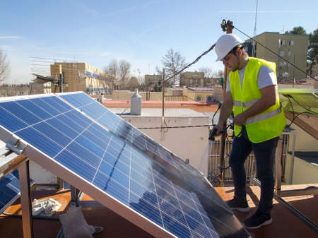 Caucasian attractive young technician cleaning solar panels with a hose. Alternative electricity source, sustainable resource concept.