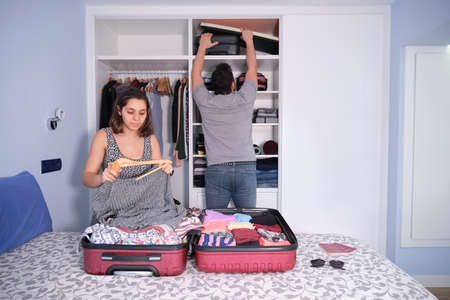 Young caucasian couple packing. He is reaching out a suitcase and she is folding a dress to pack it in her suitcase. Passports and sun glasses on the bed. Packing concept.