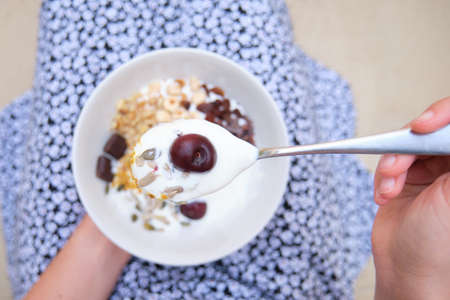 Unrecognizable woman with a cereal, yogurt, fruit bowl and spoon in focus. Healthy eating, life concept.