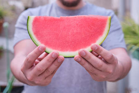 Unrecognizable man offering a seedless watermelon slice. Fruit, summer concept.