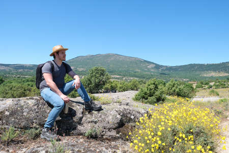 Young caucasian man with a straw hat sitting in a rock and enjoying the view. Mushroom rocks path (Ruta de las Piedras Seta), Madrid, Spain.