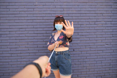 Young caucasian woman wearing face mask and keeping a meter of distance with other person. Coronavirus prevention concept. Foto de archivo