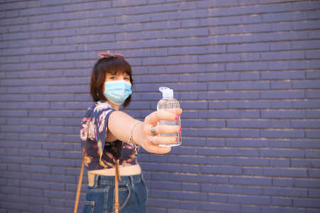 Young caucasian woman wearing face mask and showing sanitizer gel to the camera. Coronavirus prevention concept.