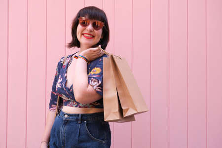 Young caucasian woman with sunglasses smiling and holding shopping bags over pink background. Happiness and shopping concept.