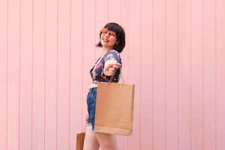 Young caucasian woman with sunglasses smiling and showing a shopping bag to the camera over pink background. Happiness and shopping concept.