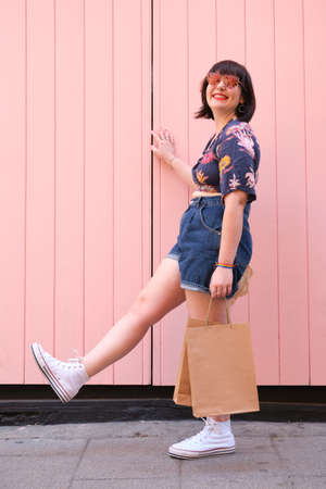 Young caucasian woman with sunglasses smiling and holding shopping bags over pink background, vertical image. Happiness and shopping concept.