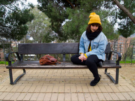 Young adult woman with yellow woolen cap sitting on a park bench thoughtful. Autumn urban concept. 免版税图像