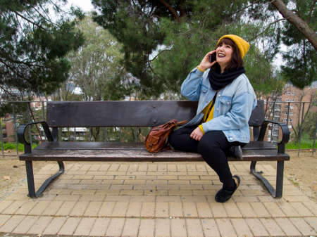 Young adult woman with yellow woolen cap sitting on a park bench talking on the phone and laughing. Autumn urban concept.