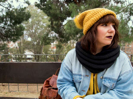 Young woman with yellow woolen cap sitting on a bench worried looking thoughtful. Autumn urban concept. Archivio Fotografico