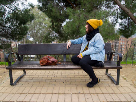 Young woman with yellow woolen cap sitting on a bench looking at a side. Autumn urban concept. Archivio Fotografico