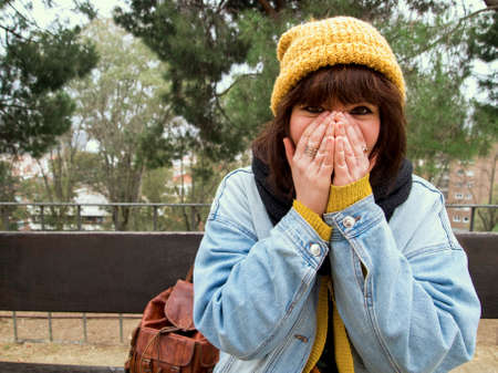 Young woman with yellow woolen cap sitting on a bench covering her face with her hands. Autumn urban concept. 版權商用圖片