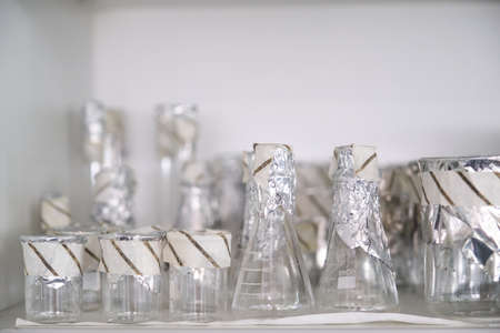 Sterile laboratory glassware with aluminum foil and autoclave tape. Real laboratory material.