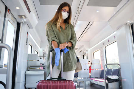 Young woman wearing face mask and putting on gloves in a train. New normal commute concept.