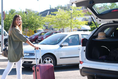 Young woman getting her suitcase out from the luggage boot of the car. Holidays concept. Standard-Bild
