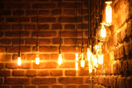 Orange retro lamps hanging on a dark black brick wall background. Vintage incandescent Edison type bulbs. Stock fotó