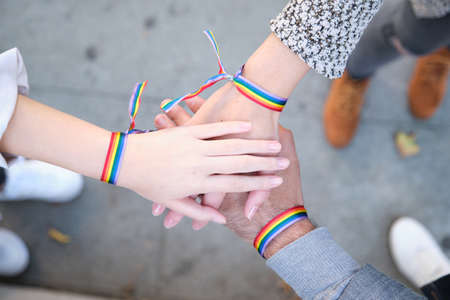 Hands of a group of three people with LGBT flag bracelets. LGBT pride celebration.