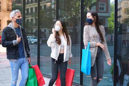 Three friends wearing face mask talking and walking on street carrying shopping bags. Shopping during pandemic times. Imagens