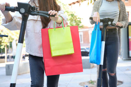 Two unrecognizable young friends carrying shopping bags and riding scooters. Urban life concept.