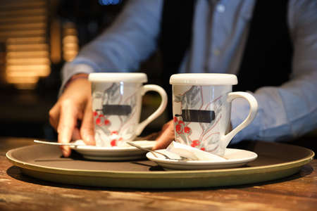 Waiter putting two cups of tea on a tray. Restaurants service concept. Stockfoto