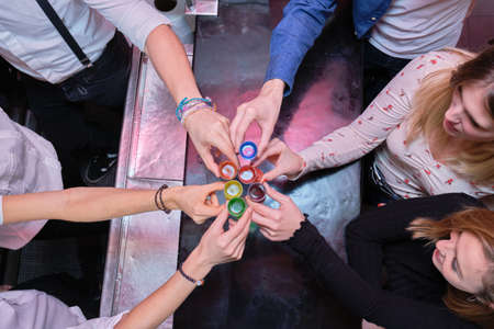 Six friends toasting with LGBT colored shot in a bar. Friendship in pubs concept. Stok Fotoğraf