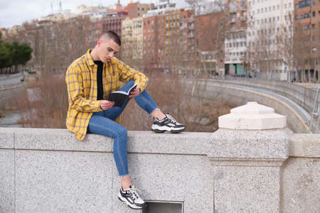 Handsome young man wearing make up, smiling and reading a book sitting on a wall. Non binary androgynous guy.