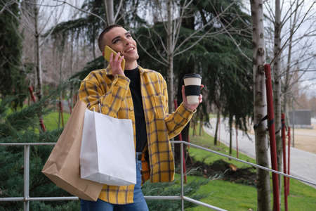 Handsome young man wearing make up, smiling while is speaking on the smartphone, holding a cup of coffee and shopping bags. Non binary androgynous guy.