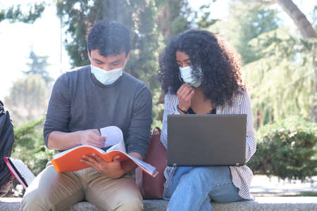 Two latin students wearing protective face mask studying together sitting on a bench outdoor. New normal at university campus.
