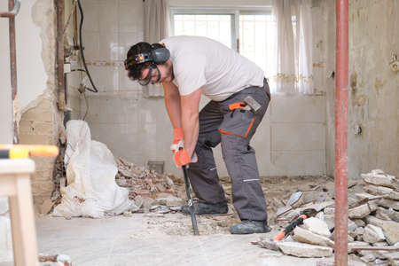 Builder digging up the house floor, lifting up old tiles with a crowbar. House renovation.