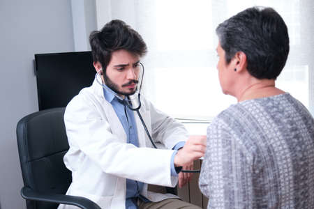 Young doctor health care provider performing a physical exam and listening to mature woman patient heart and lungs with a stethoscope.