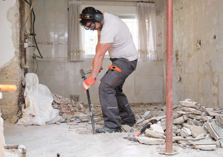 Builder digging up the house floor, lifting up old tiles with a crowbar and a hammer. House renovation.