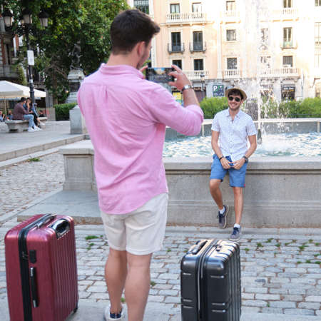 Man taking a picture of his friend at fountain in a city square.