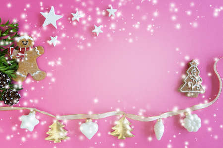 Christmas decoration with stars, ligths and gingerbread man on pink background, copy space