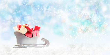 Wooden sledge with gift packages in the snow against a blue background