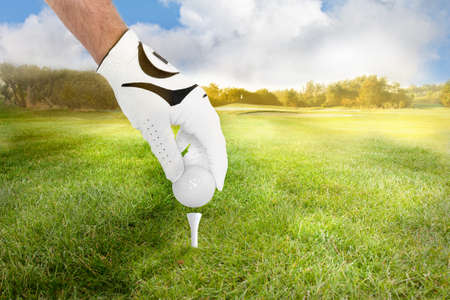 Hand of a golfer places golf ball on the tee